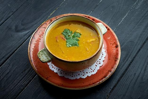 Sopa tradicional marroquina - harira, sopa de lentilha amarela com coentro em um prato vermelho sobre um fundo preto de madeira. sopa dietética