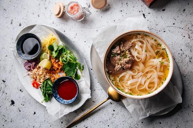 Sopa tradicional vietnamita pho bo com coberturas