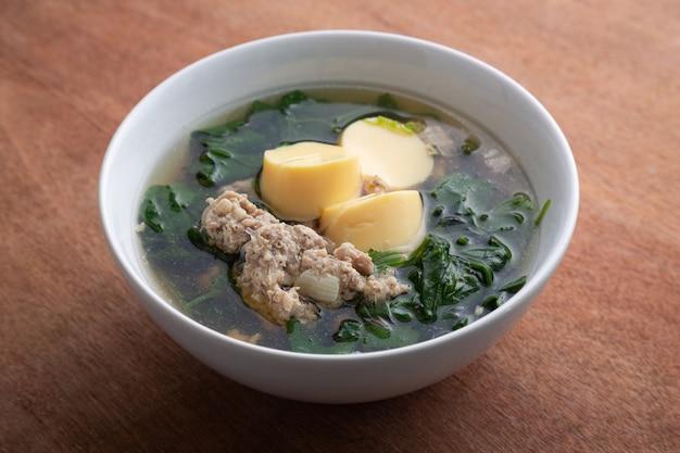 Sopa triturada fervida da carne de porco e do tofu com cabaça na bacia branca na tabela de madeira, alimento tailandês, alimento saudável.