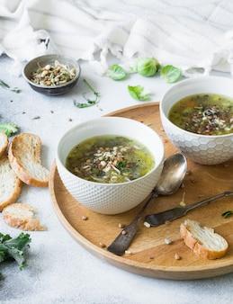 Sopa vegan vegetal verde de keil, couve de bruxelas, abobrinha, alho-poró com várias sementes germinadas e couve com croutons na bandeja de madeira