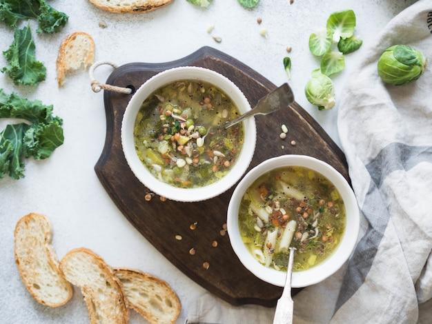 Sopa vegan vegetal verde de keil, couve de bruxelas, abobrinha, alho-poró com várias sementes germinadas e couve com croutons vista superior