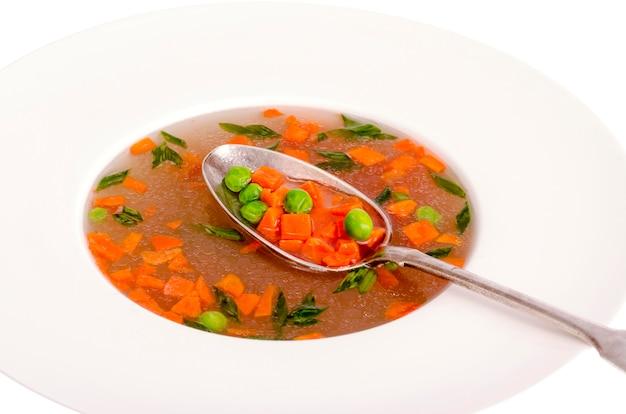 Sopa vegetal dietética com cenouras, ervilhas e cebolas verdes.