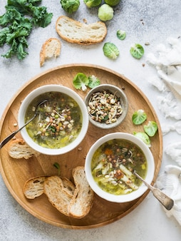 Sopa vegetal verde do vegetariano do keil, couves de bruxelas, abobrinha, alho-porro com várias sementes germinadas e brotos com o pão torrado na bandeja de madeira. vista do topo