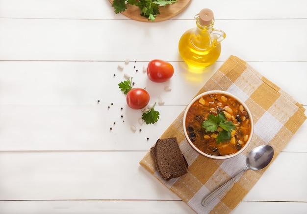 Sopa vegetariana com feijão, azeitonas e tomates em uma xícara de cerâmica, azeite de oliva em um guardanapo de linho amarelo sobre uma mesa de madeira branca.