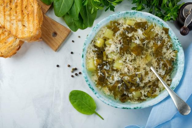 Sopa vegetariana simples de azeda, batata e ovos batidos em uma superfície clara