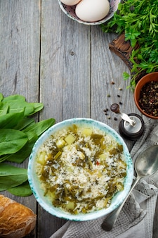 Sopa vegetariana simples feita de azeda, batata e ovos batidos em uma velha superfície de madeira