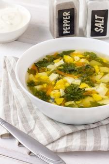 Sopa verde com ovos em uma mesa branca