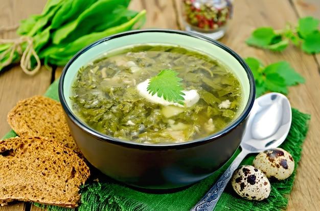 Sopa verde de azeda, urtiga e espinafre em uma tigela, colher, pão, pimenta, ovos de codorna em uma placa de madeira