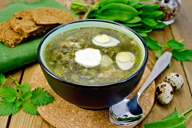 Sopa verde de azeda, urtiga e espinafre em uma tigela de ovos de codorna, pão, pimenta, colher em uma tábua de madeira