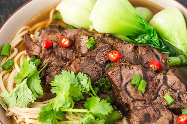 Sopa vermelha de macarrão com carne picante em uma tigela na mesa de madeira