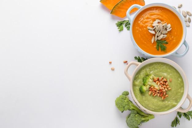 Sopas de creme coloridas com brócolis e abóbora no fundo branco, conceito de alimentação saudável, vista superior, formato horizontal, espaço para texto
