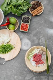 Sopas de macarrão vietnamita tradicional pho em tigelas, fundo de concreto. sopa de carne vietnamita pho bo, close-up. comida asiática / vietnamita. jantar vietnamita. refeição pho bo. vista do topo. saudável