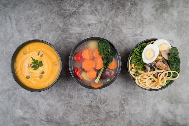 Sopas e ingredientes na vista superior da mesa de cozinha