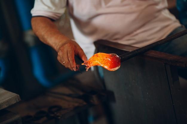 Soprador de vidro artista crafter formando pedaço de vidro. murano e burano, itália.