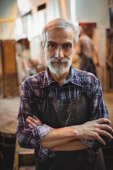 Soprador de vidro em pé com os braços cruzados na fábrica de sopro de vidro