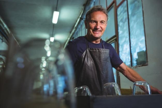 Soprador de vidro em pé na fábrica de sopro de vidro