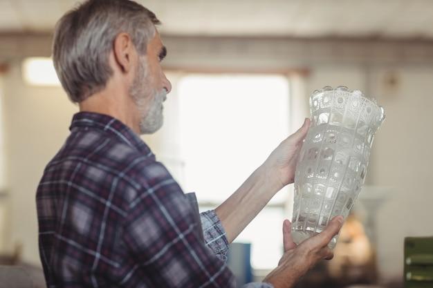 Soprador de vidro examinando artigos de vidro