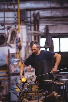 Soprador de vidro formando e moldando um vidro fundido