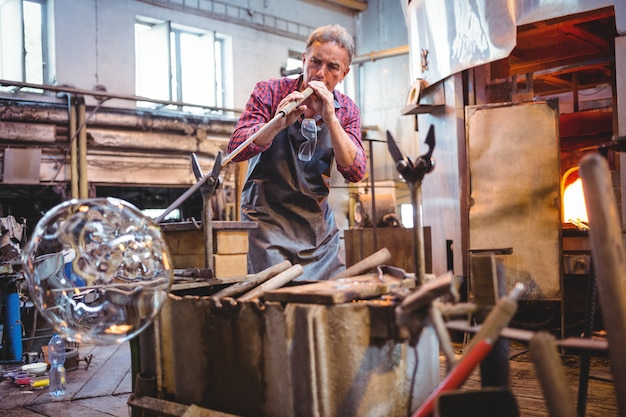 Soprador de vidro moldando um copo na zarabatana