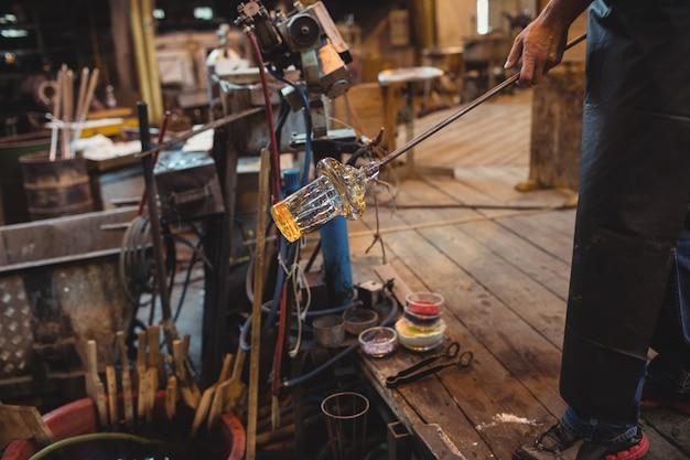 Soprador de vidro moldando um vidro fundido