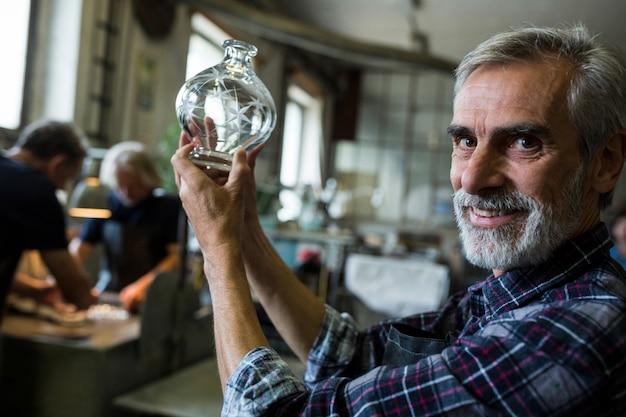 Soprador de vidro olhando vidro na fábrica de sopro de vidro