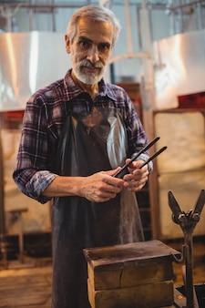 Soprador de vidro segurando pinças na fábrica de sopro de vidro