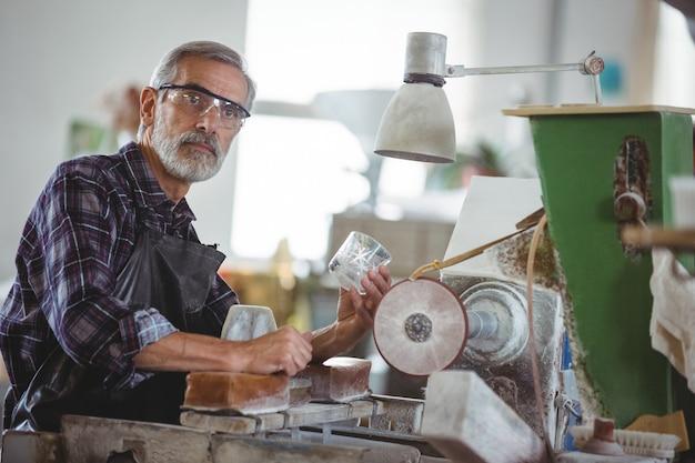 Soprador de vidro trabalhando em um copo na fábrica de sopro de vidro