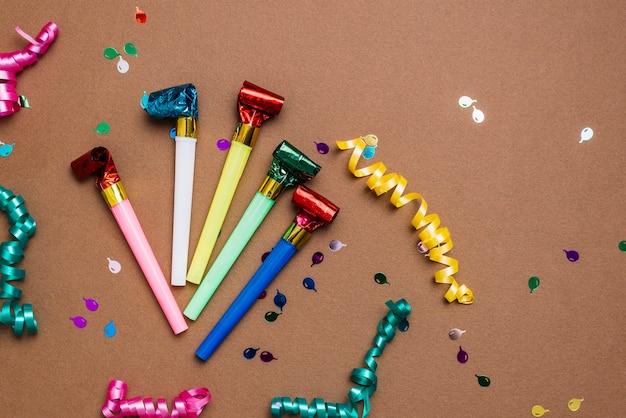 Sopradores de festa; flâmulas e confetes em fundo marrom