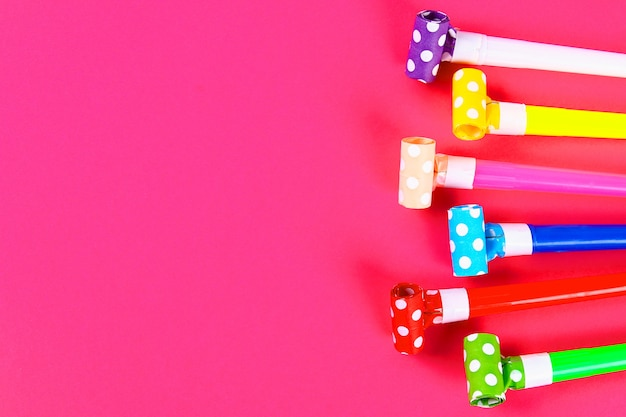 Sopradores de festa multicolor em fundo rosa. assobios de festa multicoloridos. decoração para uma festa de aniversário