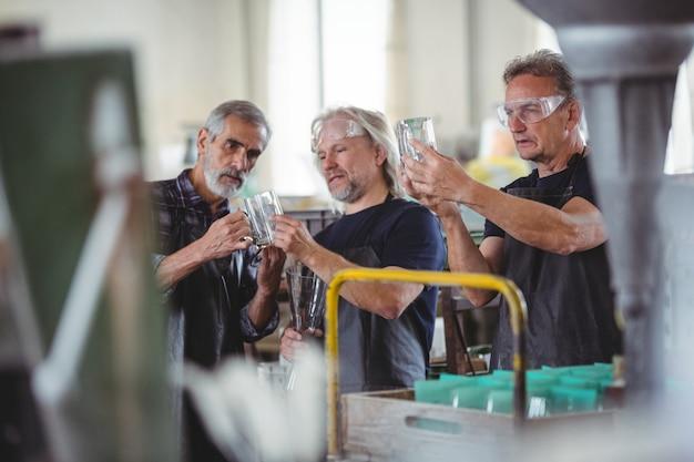 Sopradores de vidro que examinam o vaso de vidro na fábrica de sopro de vidro