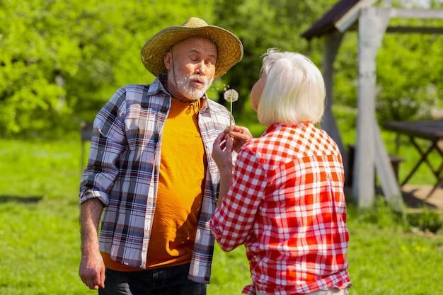 Soprando no dente-de-leão. casal fofo aposentado soprando dente-de-leão enquanto passa um tempo fora de casa