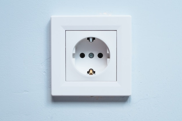 Soquete branco com contatos de aterramento em uma parede azul. conceito de consumo de eletricidade.