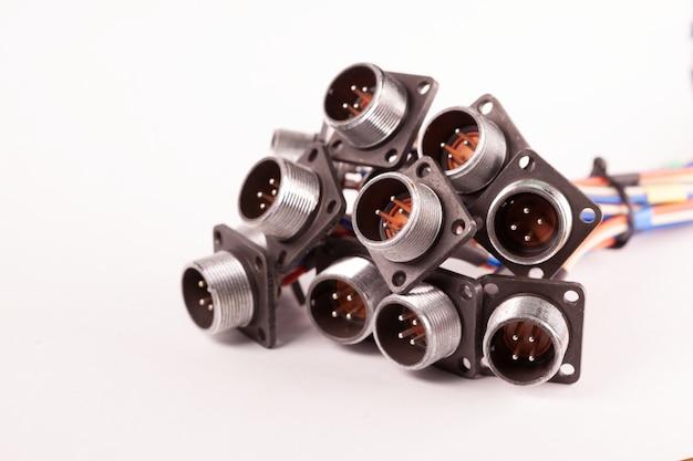 Soquetes de metal embaçados de close-up para plugues estão amontoados em uma mesa branca. conceito para a produção de televisores de computador e alto-falantes de áudio