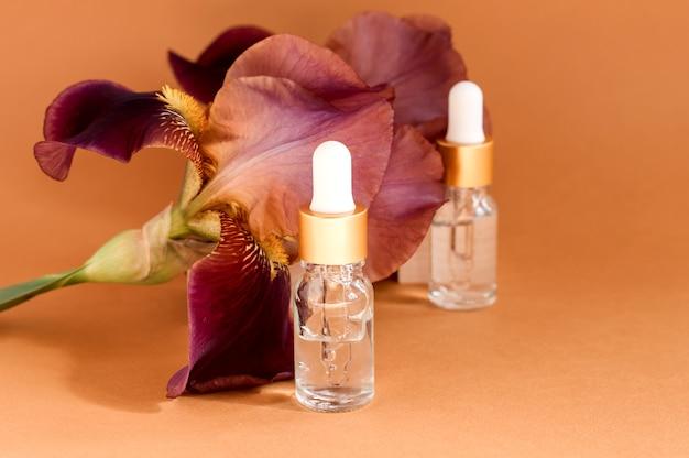 Soro com extratos florais para o cuidado da pele. conceito de spa de cuidados de rosto e corpo. cosméticos da natureza em frasco de vidro com uma pipeta e flores de íris rosa sobre fundo bege.