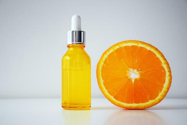 Soro de vitamina c em um frasco de cosmético e meio de laranja