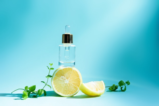 Soro facial com citrinos, limão e vitamina c em frasco de vidro com pipeta sobre fundo azul
