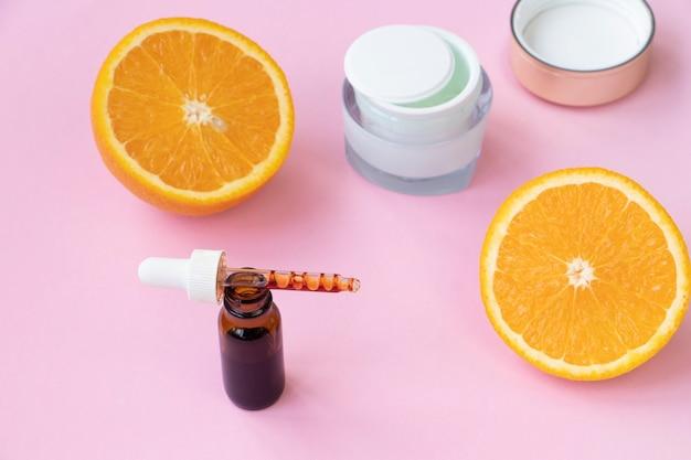 Soro facial, creme e laranja em um fundo rosa. conceito de vitamina c em cosmetologia e cosméticos.