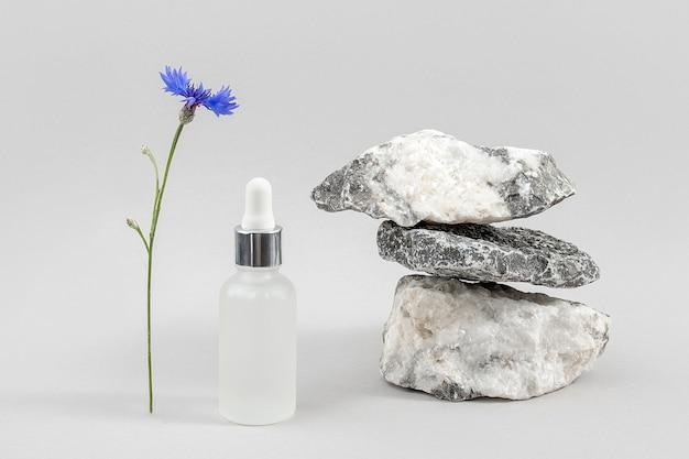 Soro facial em frasco de vidro transparente com pipeta, pilha de pedras e flor azul centáurea