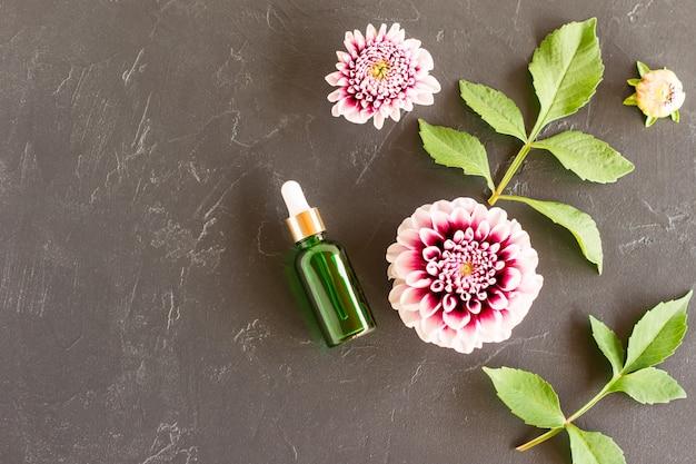 Soro facial em frasco verde-vidro com pipeta em fundo preto com dálias roxas e folhas. vista do topo. copie o espaço.