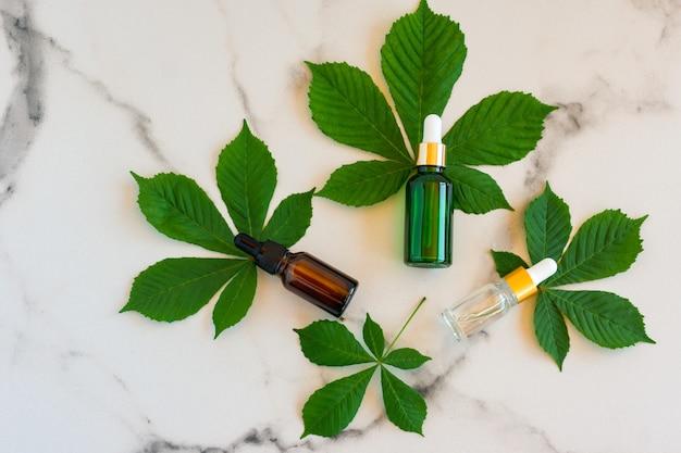 Soro facial em frascos de vidro com uma pipeta, folhas verdes sobre fundo de mármore. pacote de etiqueta em branco para maquete de marca. conceito de cosméticos de primavera. produto de beleza orgânico natural.