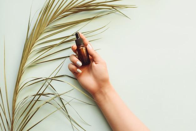 Soro hidratante no fundo de uma folha de palmeira em uma mão de meninas. fundo azul pastel. modelo de publicidade, blog. o conceito de cuidados com a pele