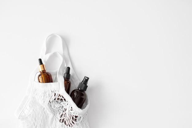 Soro, óleo, ácido e loção em um conta-gotas marrom com a pipeta em um saco de rede plano em branco. produtos de spa. saco de compras ecológico e reutilizável. cosmético orgânico e natural. beleza, cuidados com a pele. desperdício zero.