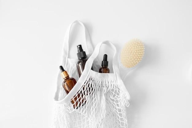 Soro, óleo, ácido, loção em vidro conta-gotas marrom com pipeta, escova corporal em saco de rede plano deitado no branco. produtos de spa. saco de compras ecológico reutilizável. cosmético orgânico e natural. beleza, cuidados com a pele. desperdício zero