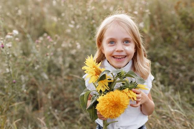 Sorri uma menina de 5 anos com flores amarelas brilhantes em um fundo de verão
