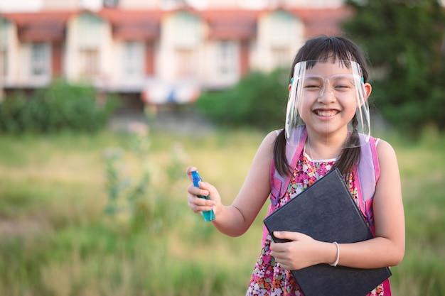 Sorria aluna usando escudo facial durante ela voltar para a escola após a quarentena de 19-covid.