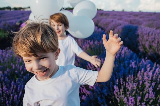 Sorria duas crianças correndo em um campo de lavanda com balões brancos ensolarados, dia ao ar livre, vista frontal
