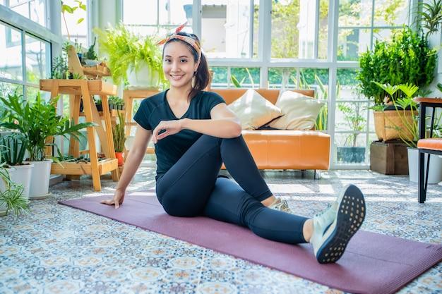 Sorria feliz bela jovem mulher asiática, exercícios de alongamento em casa