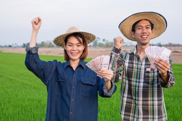 Sorria feliz casal de agricultores asiáticos segurando notas tailandesas e levante a mão em pé na fazenda de arroz
