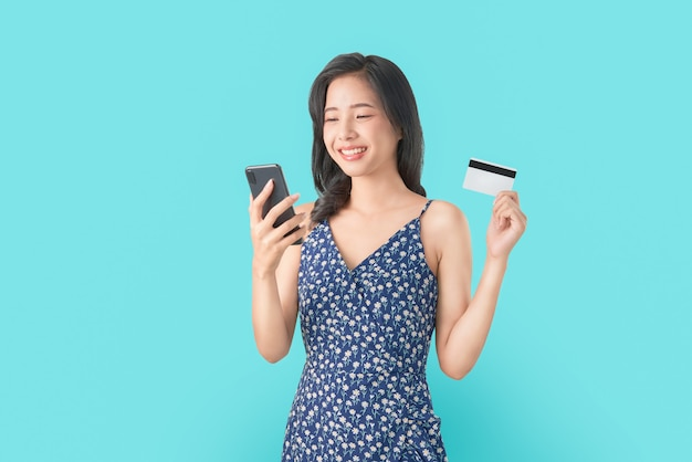 Sorria felizmente mulher asiática segurando smartphone e cartão de crédito, compras on-line sobre fundo azul.