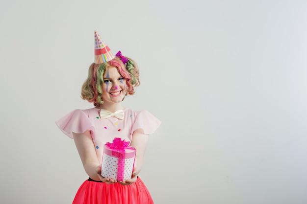 Sorria garota adolescente em traje de palhaço com caixa de presente